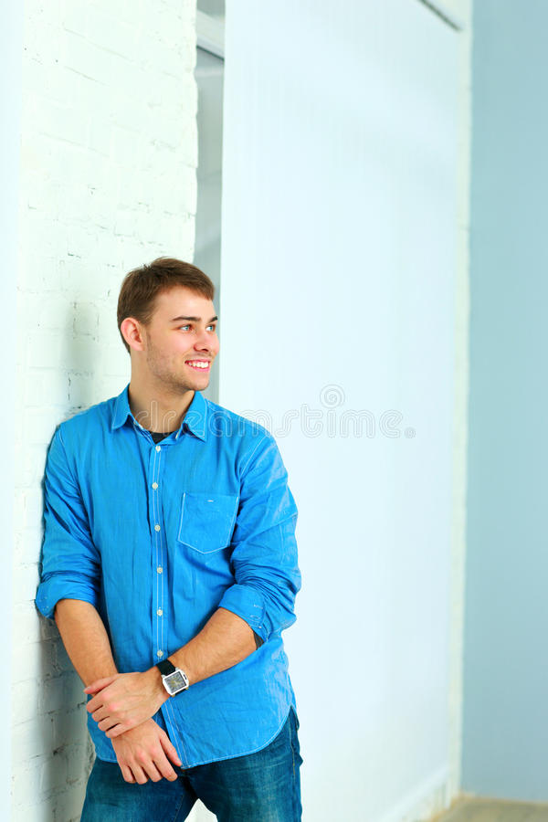 Portait van jonge gelukkige zakenman status dichtbij de muur royalty-vrije stock afbeelding