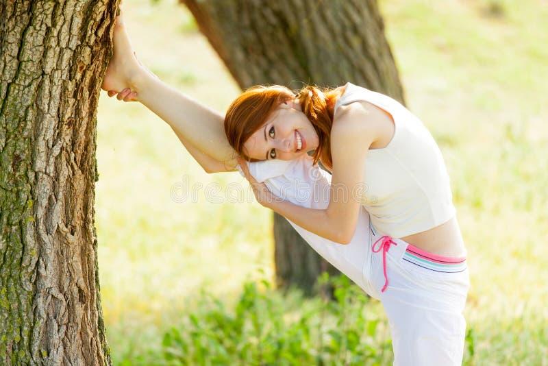 Portait van mooie jonge vrouw die joga op prachtige tre doen stock fotografie