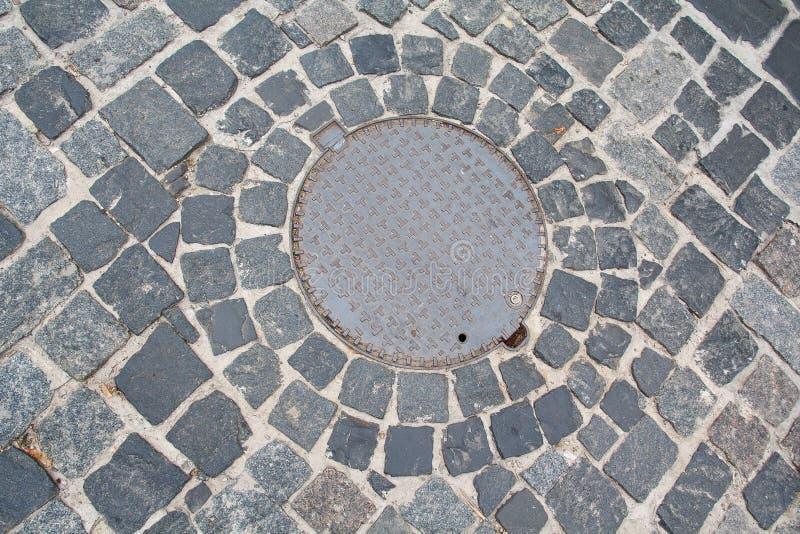 Portal do esgoto do metal no pavimento de pedra foto de stock