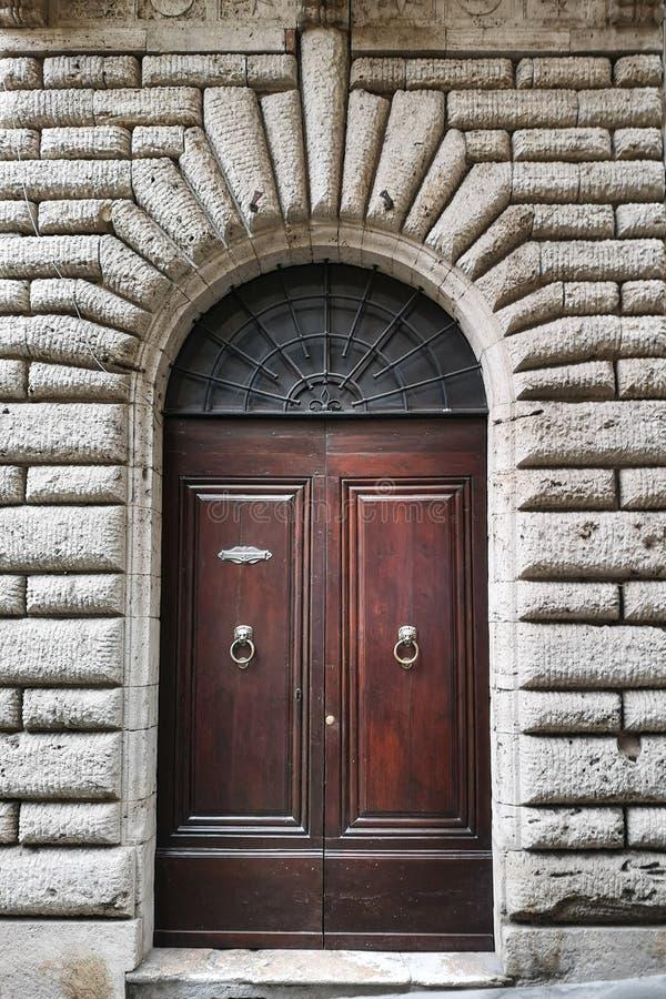 Portale di legno antico con l'arco di pietra scolpito di una fortezza medievale italiana fotografia stock