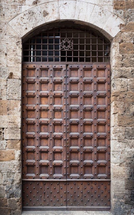 Portale di legno antico con l'arco di pietra di una fortezza medievale italiana fotografia stock
