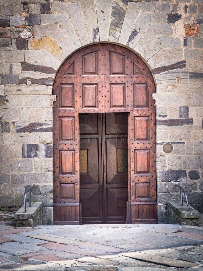 Portale di legno antico con l'arco di pietra di una fortezza medievale italiana immagine stock libera da diritti