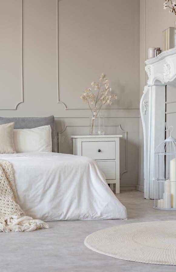 Portale di legno bianco del camino in bella camera da letto interna con gli strati bianchi su letto a due piazze fotografie stock libere da diritti
