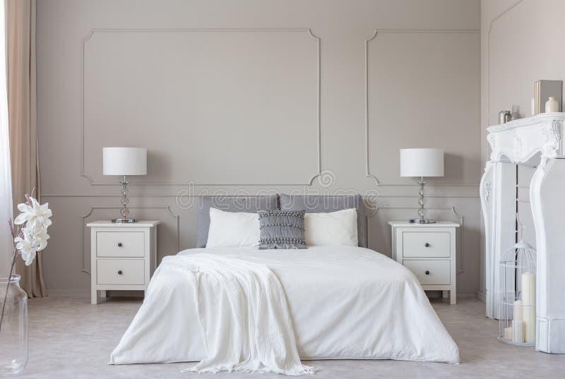 Portale di legno bianco del camino nell'interno luminoso della camera da letto, spazio della copia sulla parete grigia vuota fotografia stock libera da diritti