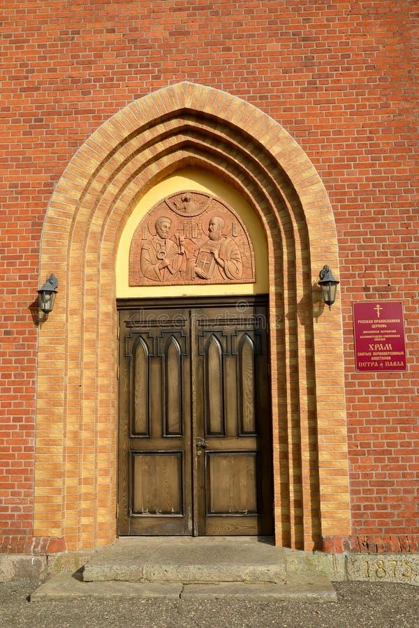 Portale incassato dell'entrata principale Krasnoznamensk, regione di Kaliningrad Testo russo - tempio degli apostoli di prima man immagine stock