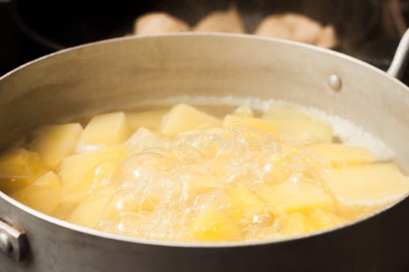 Portando alle patate bollite prontezza tagliate Pentola di alluminio immagine stock libera da diritti