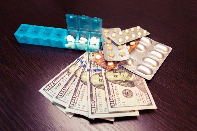 Portapillole, pillole e compresse sui soldi del dollaro sulla tavola di legno scura Spese della medicina Alti costi del concetto  fotografia stock