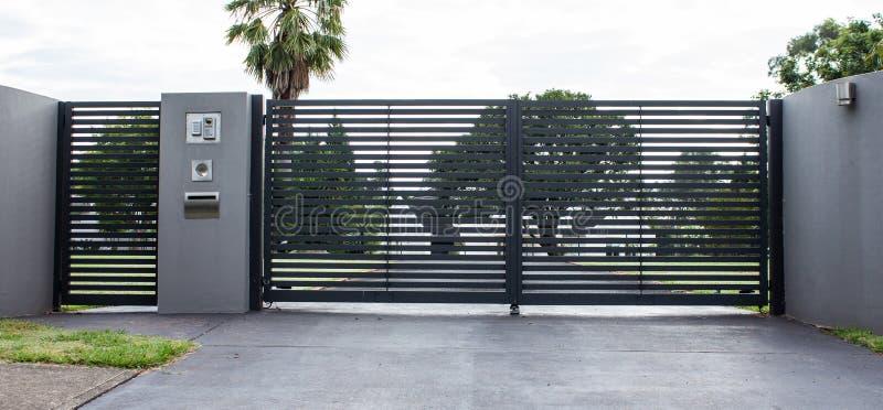 Portar för ingång för metallkörbanaegenskap ställde in i konkret staket med trädgårdträd i bakgrund royaltyfri fotografi