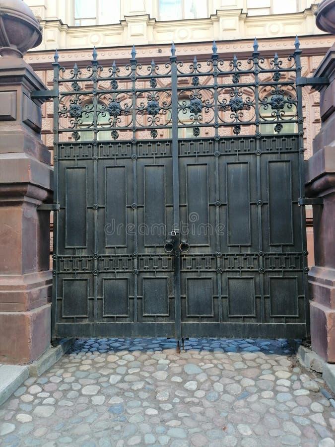 Portar med prydnader på ingången till borggården av byggnaden royaltyfri fotografi