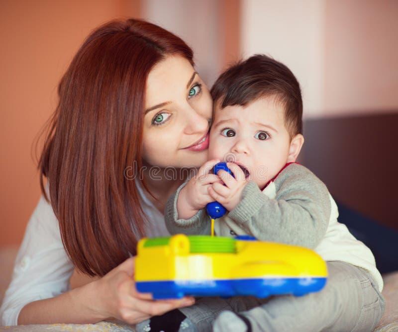 Portarit der hübschen Mutter und ihres wenig Babysohnspielens lizenzfreie stockfotos