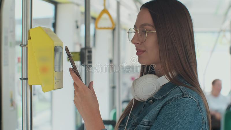 Portarit of a young smiling woman paying conctactless with smartphone for the public transport in the tram. Portarit of a young smiling woman paying stock images