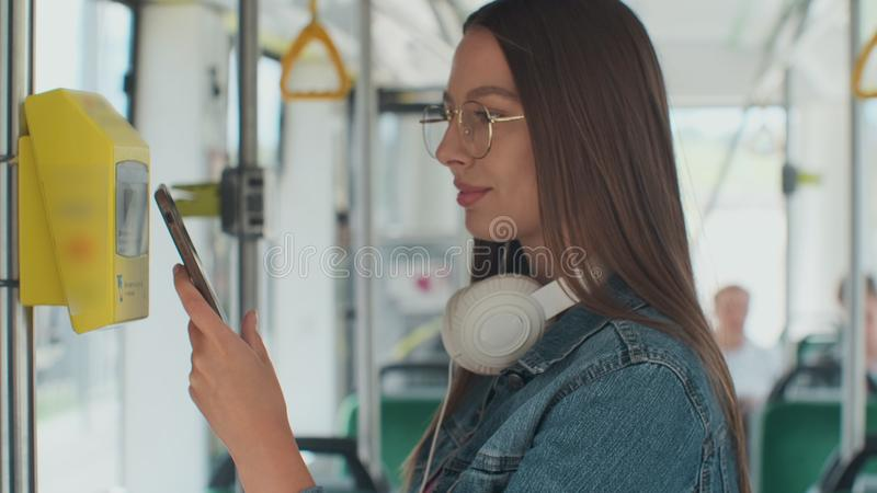 Portarit of a young smiling woman paying conctactless with smartphone for the public transport in the tram. Portarit of a young smiling woman paying stock photography