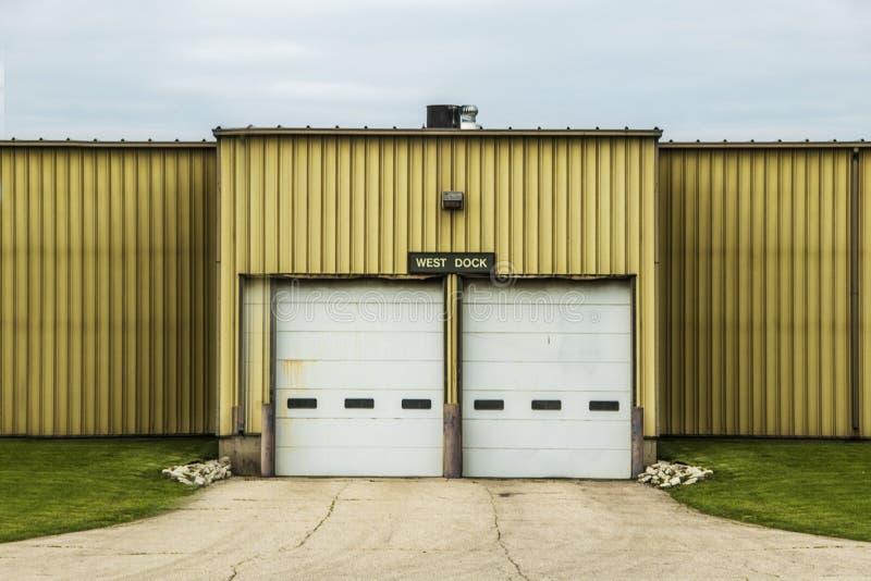 Portas da doca de carga em uma construção amarela do armazém foto de stock
