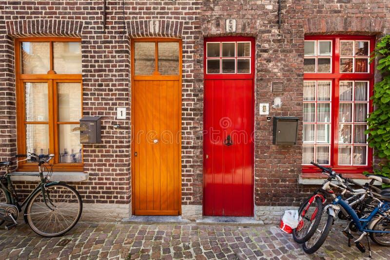 Portas de casas e de bicicletas velhas na cidade europeia Bruges (Bruges foto de stock