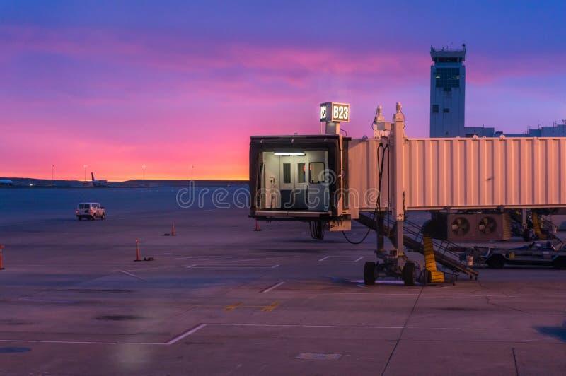 Portas de Jetway sobre e pista de decolagem do aeroporto no nascer do sol com a torre de controlo do voo no fundo imagem de stock
