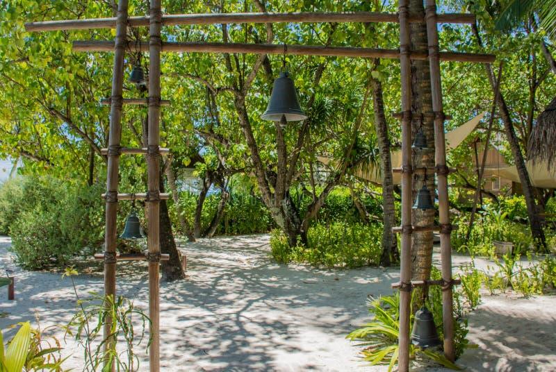 Portas de madeira com o sino do metal perto da entrada do restaurante na ilha tropical imagens de stock royalty free