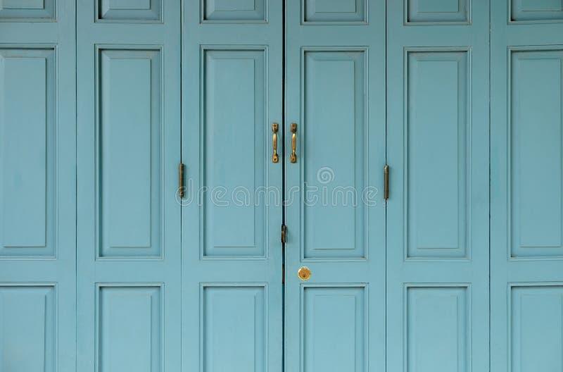 Portas douradas antigas fechados na porta velha azul imagem de stock royalty free