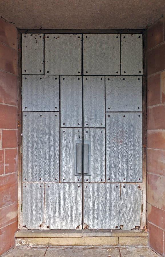 Portas duplas fechadas cobertas por placas de aço reforçadas numa parede de pedra exterior fotos de stock