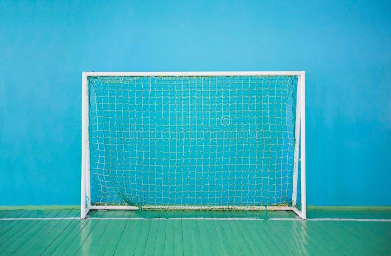 Portas para o mini-futebol no fundo da parede azul imagem de stock