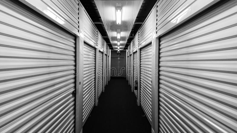 Portas preto e branco da unidade de armazenamento do auto do metal em cada lado de um corredor imagem de stock royalty free