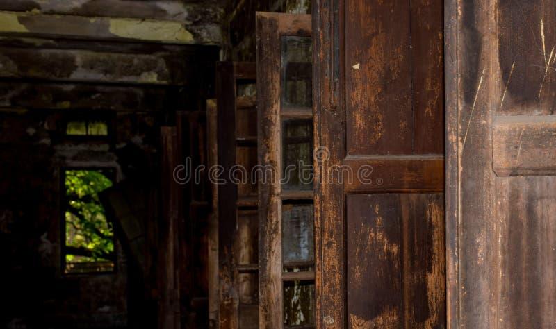 Portas velhas de dano janelas em uma casa escura de dano velho fotos de stock