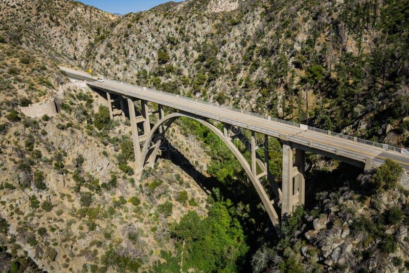 Portata del ponte dell'arco sopra la valle boscosa fotografia stock