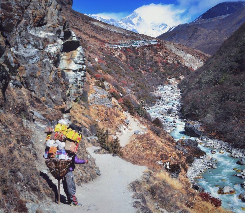 Portatore della montagna che sostiene onere gravoso in Himalaya immagine stock libera da diritti