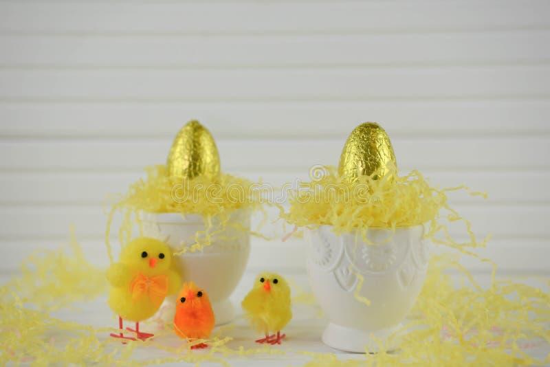 Portauova con le uova di Pasqua dorate del cioccolato di colore su bianco fotografie stock libere da diritti