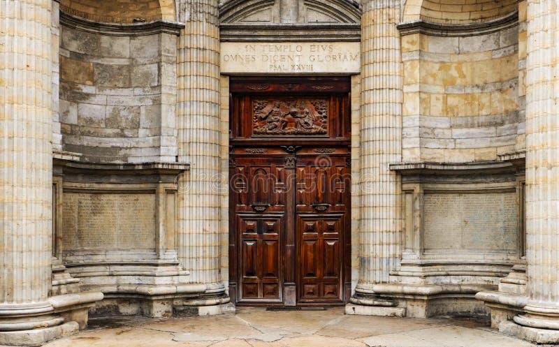 Porte à deux battants en bois lourde en dehors d'une vieille église avec des soulagements et des inscriptions religieux photo libre de droits