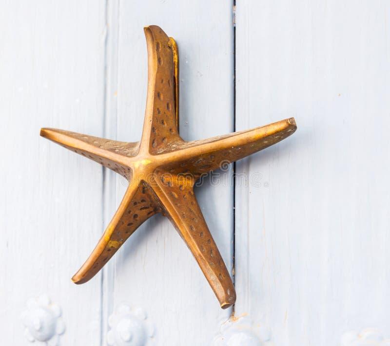 Porte avec le heurtoir en laiton sous forme d'étoile de mer, belle en images libres de droits