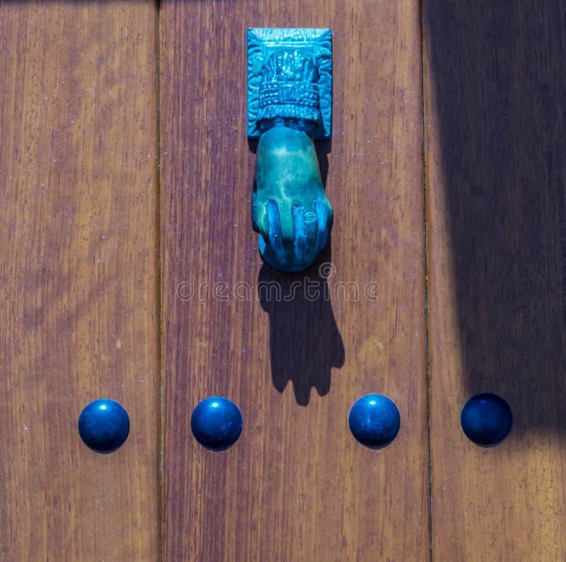 Porte avec le heurtoir en laiton sous forme de main, bel entran photographie stock