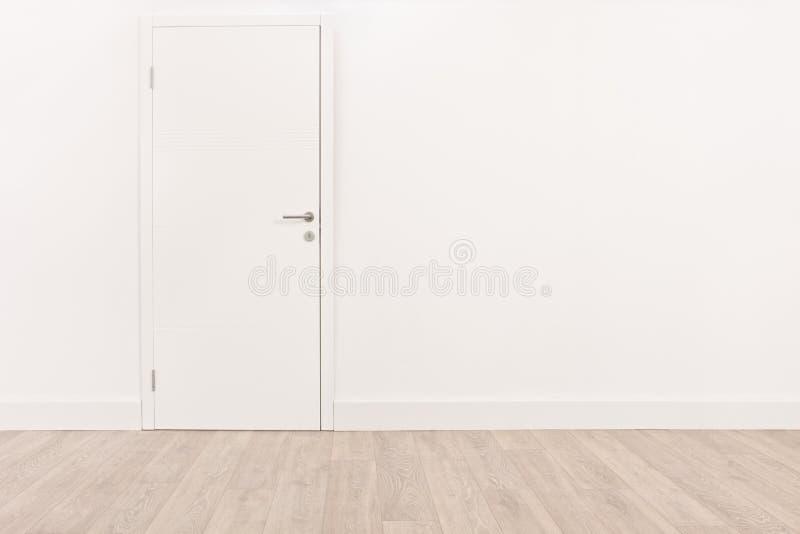 Porte blanche et un plancher en bois dur brun clair photo stock