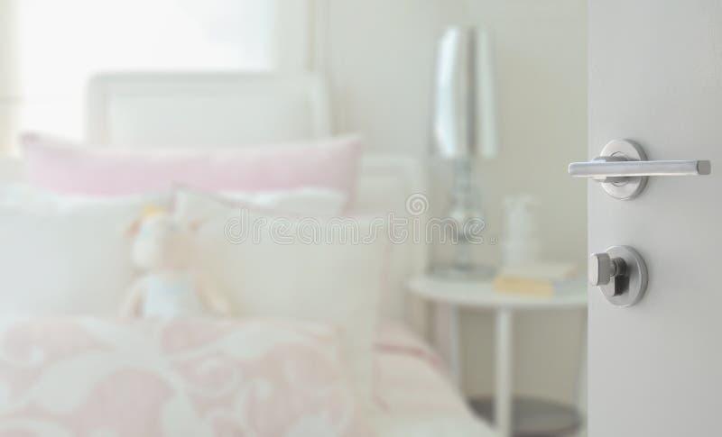 Porte blanche ouverte à la chambre à coucher confortable avec les oreillers roses et blancs dessus image libre de droits