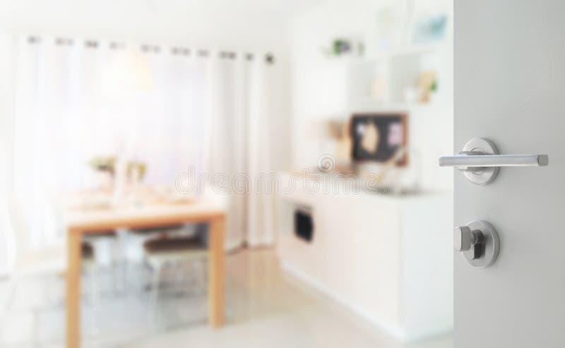 Porte blanche ouverte à la cuisine moderne avec la table de salle à manger à côté de l'office images stock