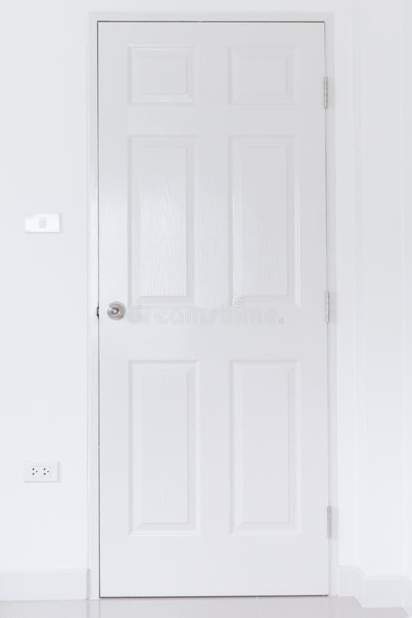 Porte blanche sur le mur blanc avec le bouton de porte inoxydable, poignée sur la porte en bois blanche, fin vers le haut de l'in photo libre de droits