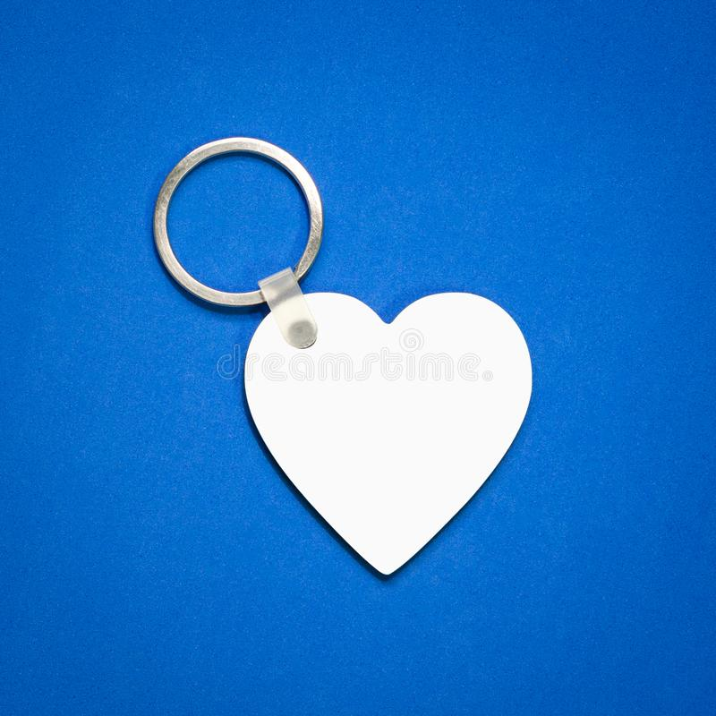 Porte-clés blanc sur le fond bleu Cha?ne principale pour votre conception Accessoire ou souvenir accrochant Forme de coeur photo stock