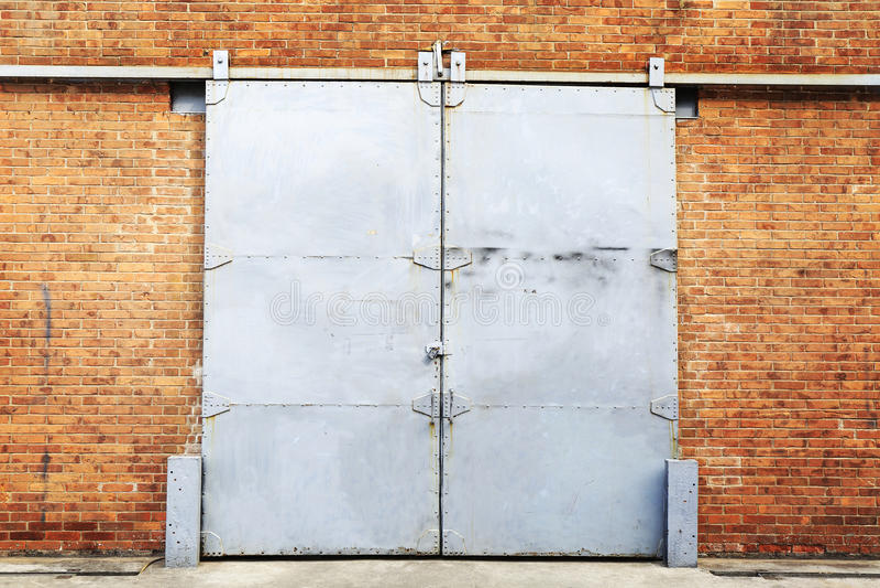 Porte coulissante en métal dans le mur de briques photo stock