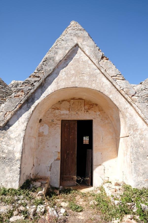 Porte d'entrée de vieille maison abandonnée de Trulli avec les toits coniques multiples dans le secteur de Cisternino/d'Alberobel photographie stock