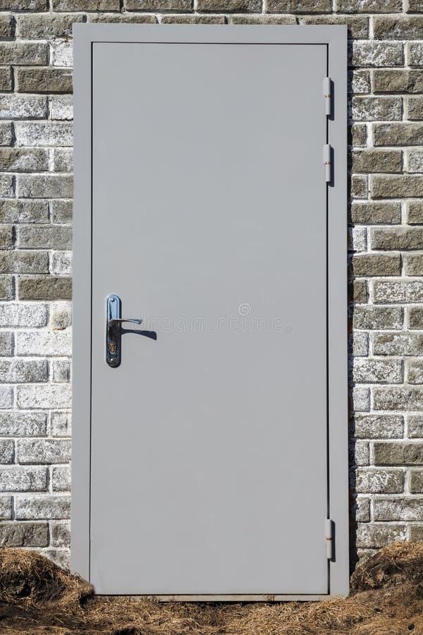 Porte d'entrée solide grise en métal construite dans un mur de briques d'une soute image stock