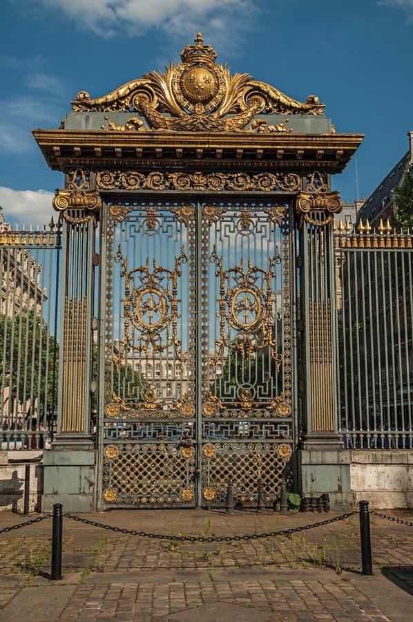 Porte d'or et barrière de fer largement décorées sous le ciel bleu ensoleillé à Paris photo stock