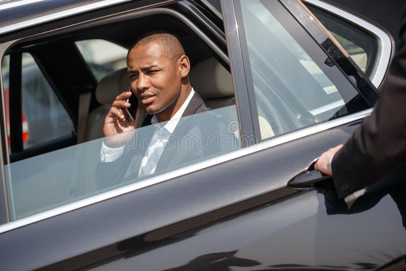 Porte d'ouverture de sécurité au jeune homme d'affaires s'asseyant dans la voiture parlant sur le strabisme joyeux de smartphone  photo libre de droits
