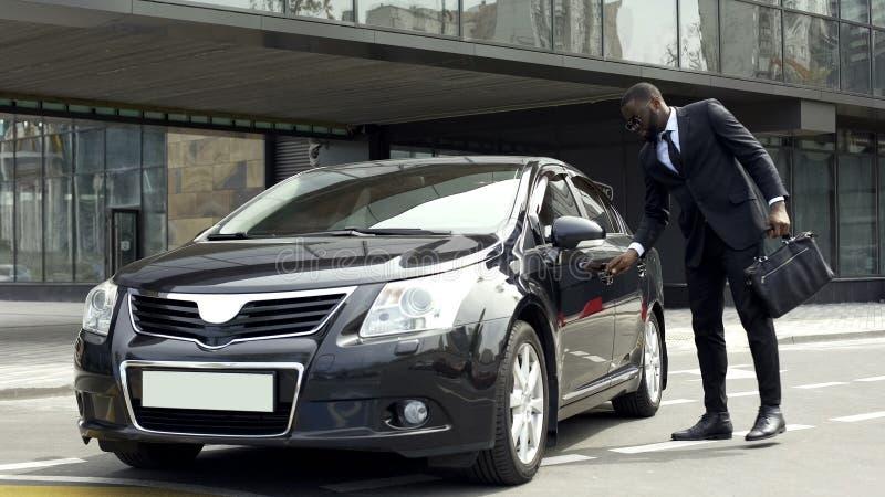 Porte d'ouverture d'homme de Rich African American de voiture de luxe avec la clé spéciale, sécurité image stock