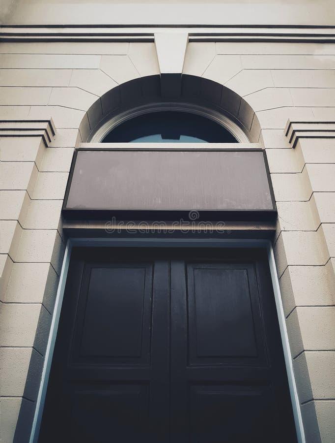 Porte de construction historique noire avec le singboard d'entrée image stock