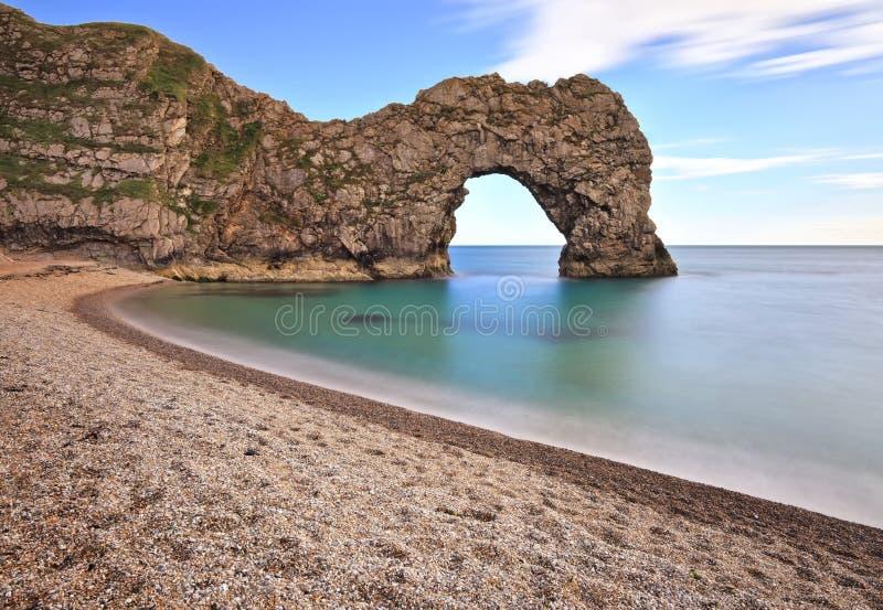 Porte de Durdle - la plage vide de bardeau à la porte de Durdle sur la côte jurassique de Dorset image stock