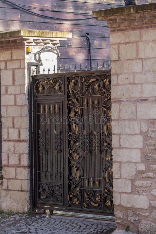 Porte de fer travaillé d'un mur de jardin et de maçonnerie pendant le matin images libres de droits
