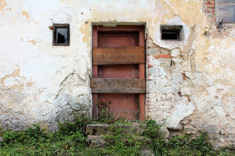 Porte di legno rosso scuro con i bordi inchiodati attraverso sulla casa con mattoni a vista dilapidata abbandonata fotografie stock libere da diritti
