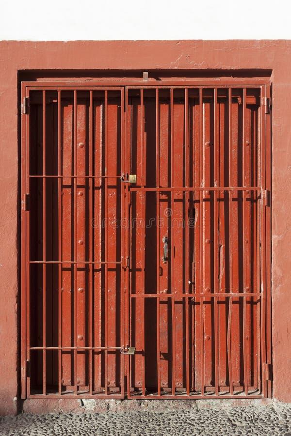 Porte en acier de glissière antique verrouillée Style ancien de porte en acier rouge étroite photos libres de droits