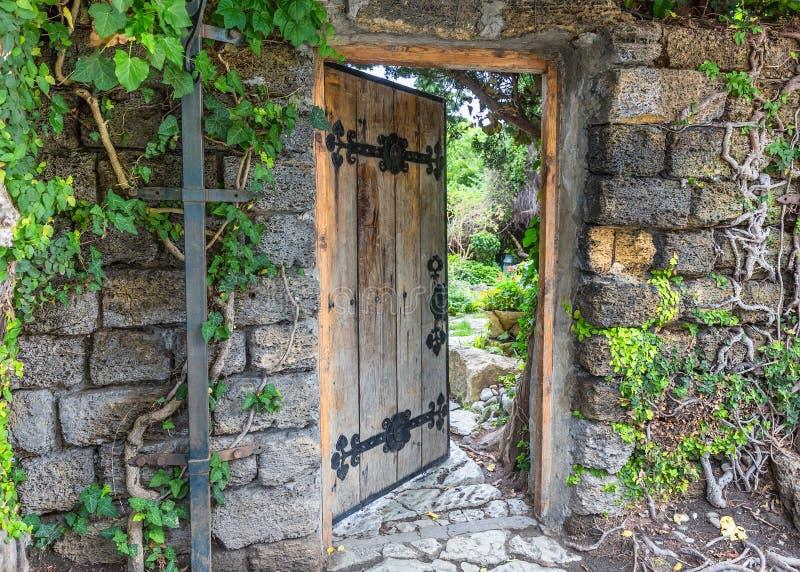 Porte en bois décorée de la pièce forgéee de fer, légèrement ouverte Mur de image libre de droits