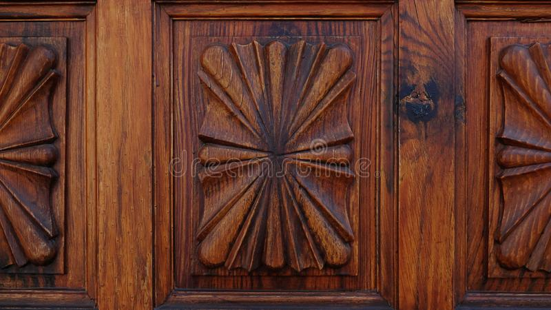 Porte en bois découpée avec des motifs stylisés classiques formant les modèles symétriques images stock