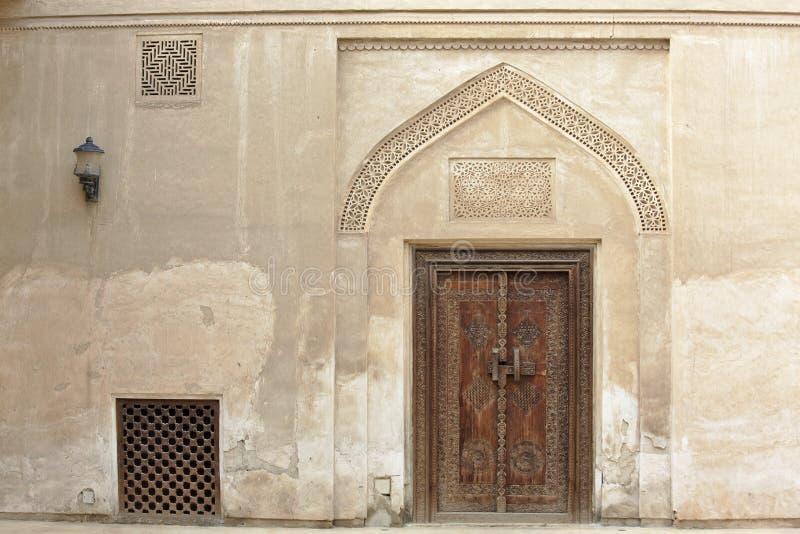 Porte en bois découpée et porte fleurie au Bahrain image libre de droits